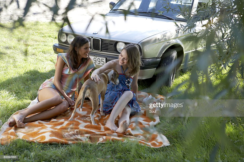 two young gilrs playing with dog : Stock Photo