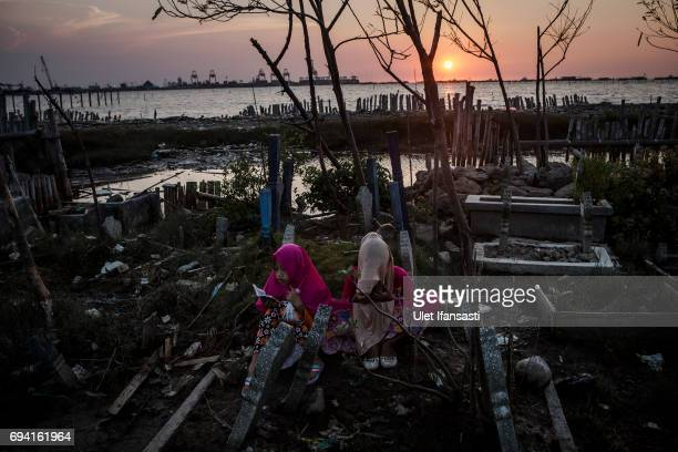 Two young girl pray at public cemetery surrounded by rising sea levels on June 8 2017 in Semarang Indonesia Indonesia is known to be one of the...