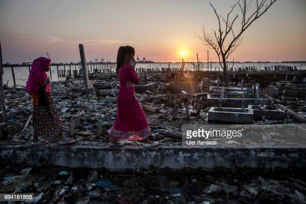 Two young girl walk through the garbage as they head to the public cemetery for pray which surrounded by rising sea levels on June 8 2017 in Semarang...