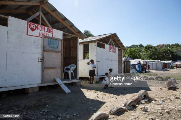 PortauPrince Haiti December 09 2012 Two young girls and a woman are standing between two first aid barracks in the refugee camp Parc Colofe in...