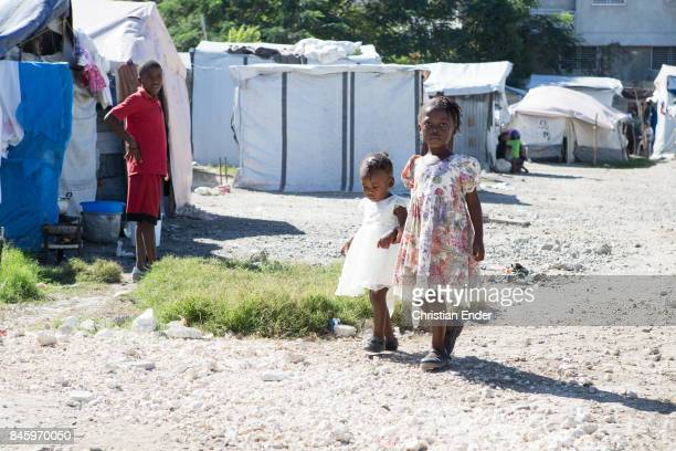 PortauPrince Haiti December 09 2012 Two young girls are walking trough the refugee camp Parc Colofe in PortauPrince The camp exist since the...
