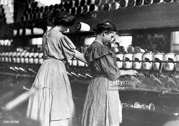 Two young girls attend to the spooling machines which wind the threads to the bobbins at the Lincoln Cotton Mill in Evansville IN 1908