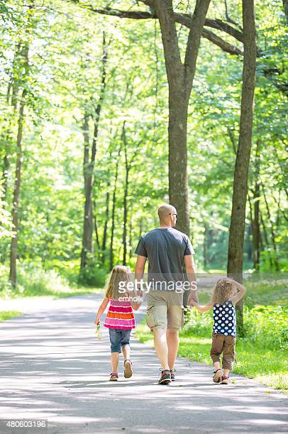 Two Young Girls & Dad Walking Through Wooded Park Trail
