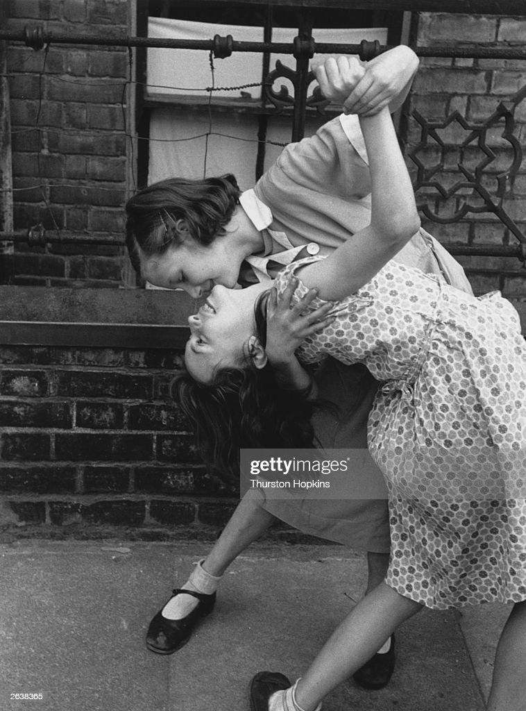 Two young girls dancing together in the street. Original Publication: Picture Post - 7230 - Children Of The Streets - pub. 1954