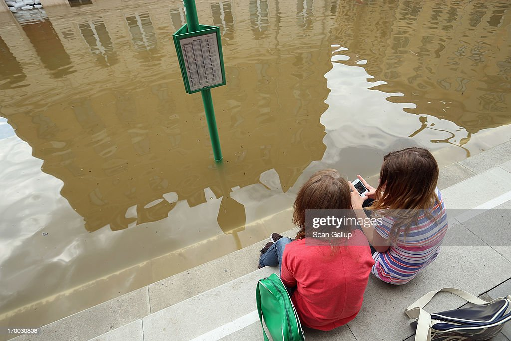 Two young girls discuss apps on their smartphones while sitting in a street flooded by the nearby Elbe river in the historic city center on June 6, 2013 in Meissen, Germany. Eastern and southern Germany are suffering under floods that in some cases are the worst in 400 years. At least four people are dead and tens of thousands have evacuated their homes.