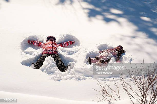 Two young girls doing snow angels, full length horizontal.