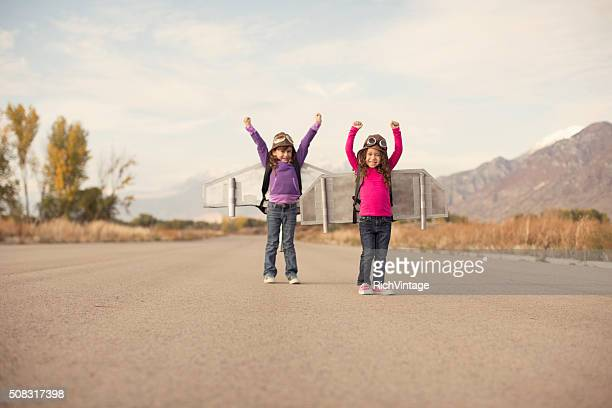 Two young girls dressed as pilots wearing jet packs