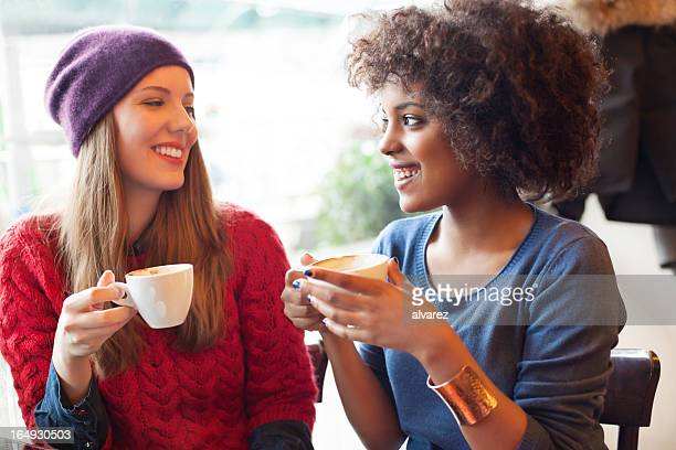 Two young girls drinking coffee together