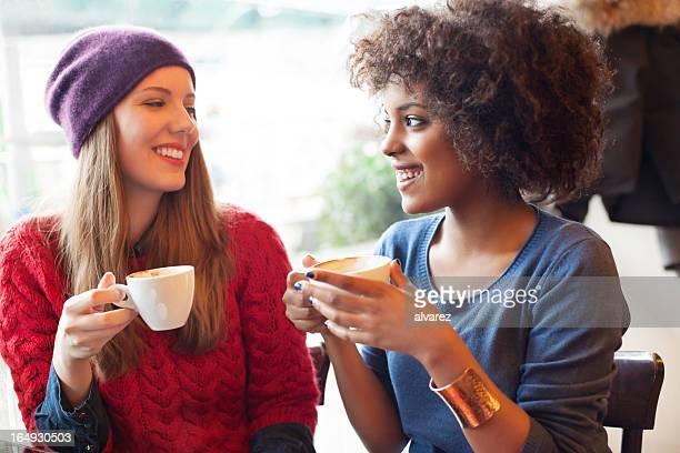 Dos chicas jóvenes bebiendo café juntos