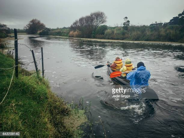 Two young girls going canoeing on a river with their father