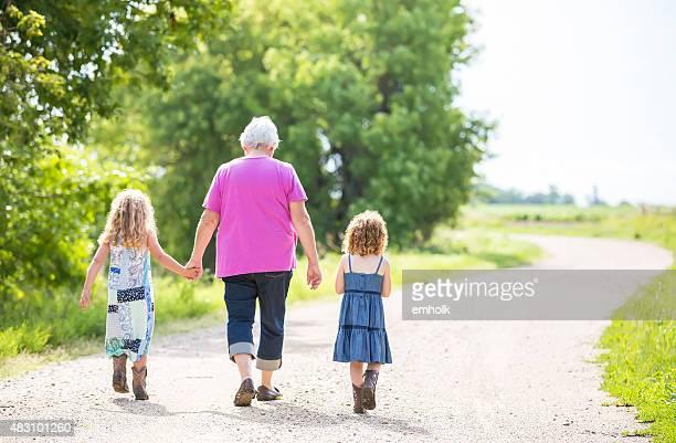Zwei junge Mädchen & Oma zu Fuß auf Ländliche Straße