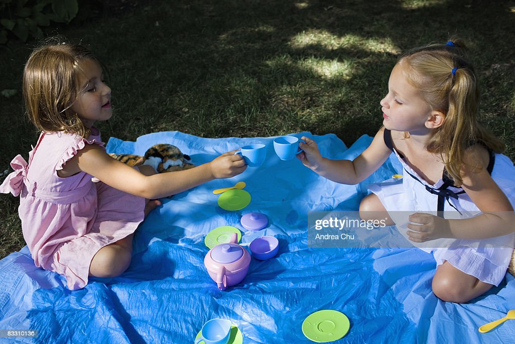 Two young girls having a outdoor tea party. : Stock Photo