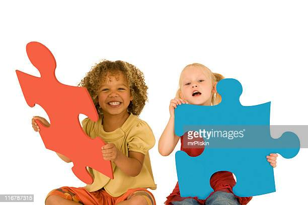 Two young girls holding large jigsaw pieces