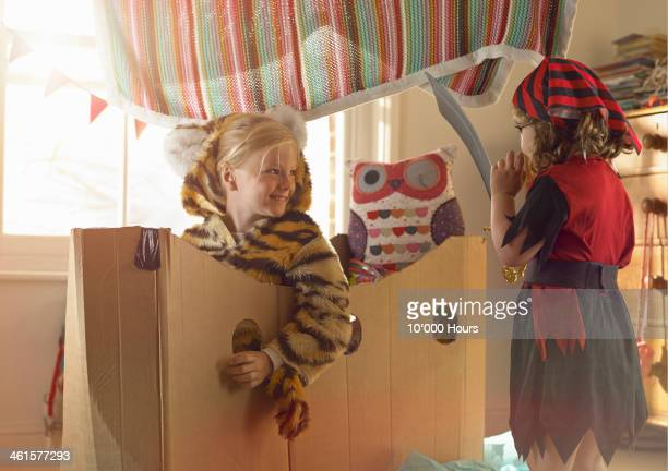 Two young girls in fancydress playing with cardbox