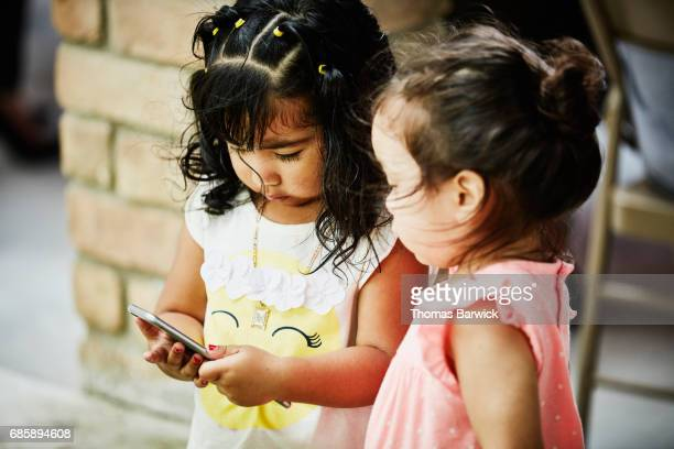 Two young girls looking at smartphone during birthday party