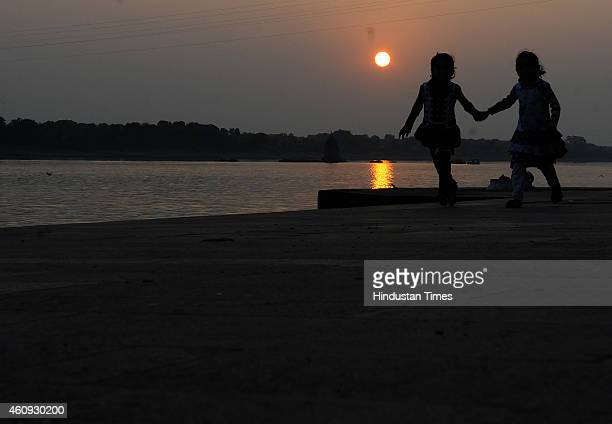 Two young girls march forward with hand in hand as the sun sets in background on the last day of 2014 on December 31 2014 in Indore India