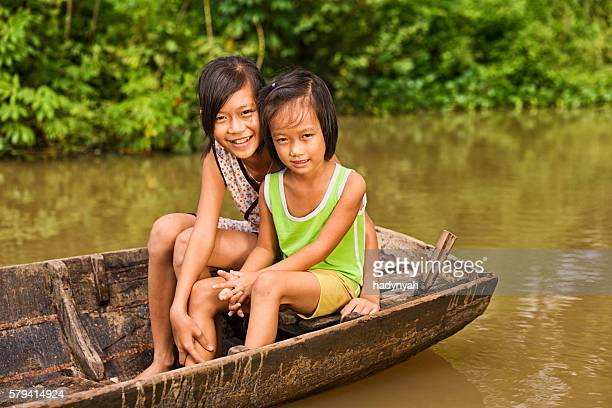 Two young girls on boat in Mekong River Delta, Vietnam