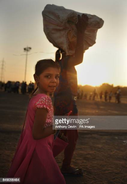 Two young girls one carrying goods on her head are seen at sunset in Ahmedabad India