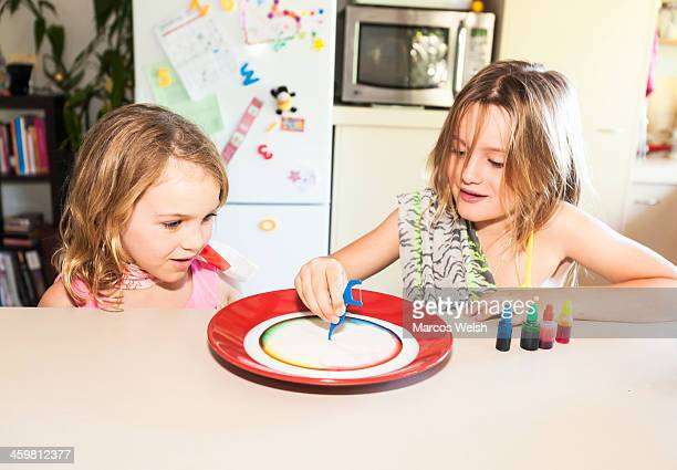 Two young girls play with milk and food coloring