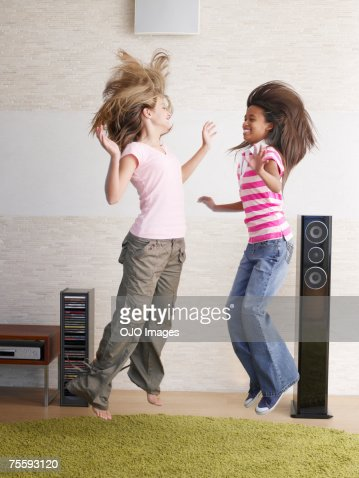 Two young girls playfully jumping around : Stock Photo