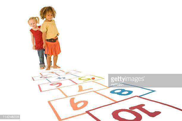 Two young girls playing Hopscotch