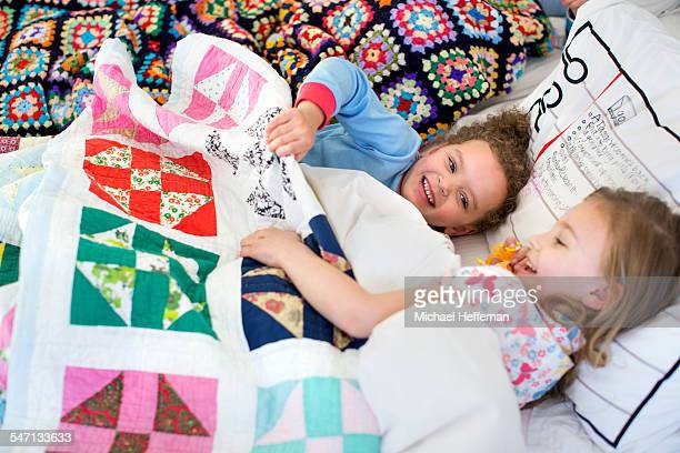 Two young girls playing in bed