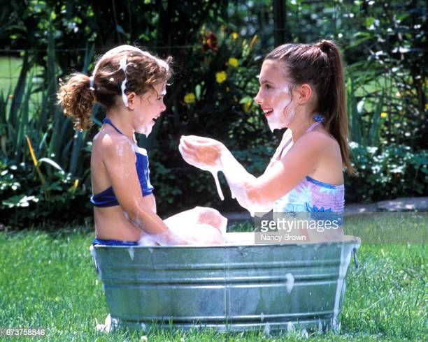 Two Young Girls Playing In Bubble Bath Outside in Tin Tub.