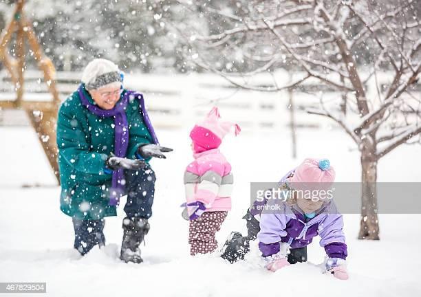 Due giovani ragazze giocare nella neve con Nonna