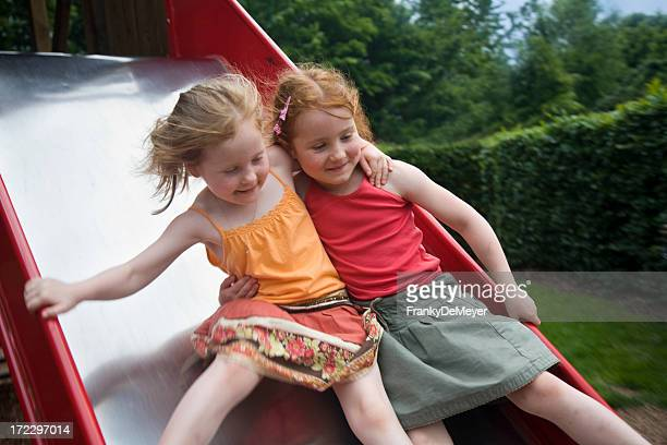 Two young girls playing on the slide together best friends