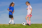 Two young girls on youth soccer teams playing against each other