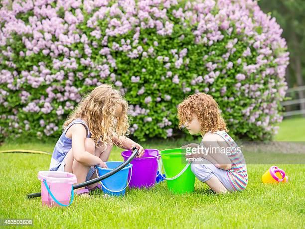 Deux jeunes filles jouant avec des seaux d'eau et Tuyau d'arrosage