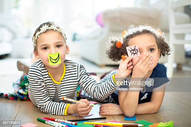 Two young girls playing with paper and pens