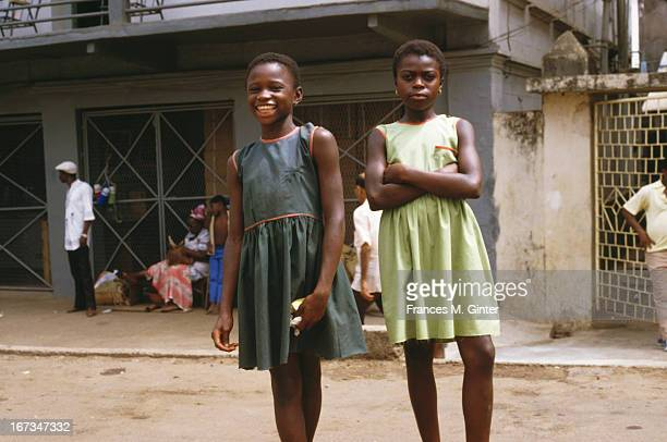 Two young girls pose for the camera along Fourah Bay Road in Freetown Sierra Leone March 1985