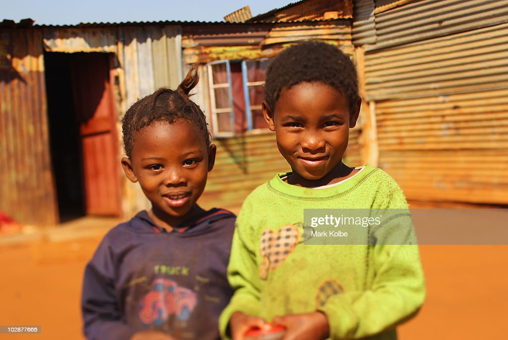 Two young girls pose outside a shanty house on June, 2010 in Rustenburg, South Africa.