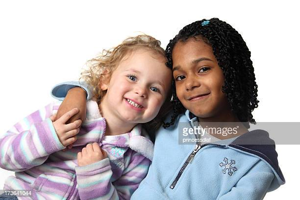 Two young girls posing together and smiling