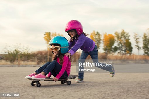 Two Young Girls Race on Skateboard