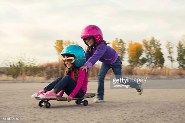 Zwei junge Mädchen mit Skateboards Rennen
