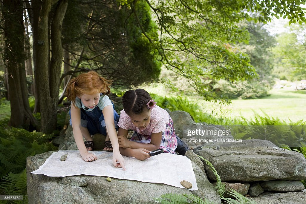 Two young girls reading a map, outdoors