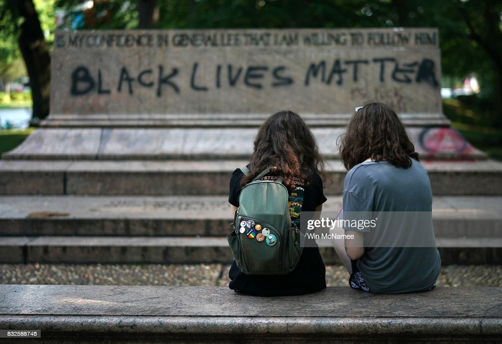 Two young girls sit at the site where a statue dedicated to Robert E. Lee and Thomas 'Stonewall' Jackson stood August 16, 2017 in Baltimore, Maryland. The City of Baltimore removed four statues celebrating confederate heroes from city parks overnight, following the weekend's violence in Charlottesville, Virginia.