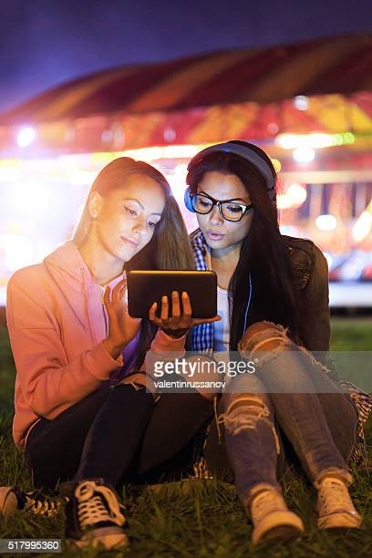 Two young girls sitting on grass using digital tablet