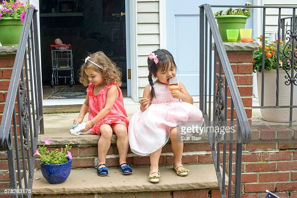 Two young girls, sitting on steps, eating ice lollies