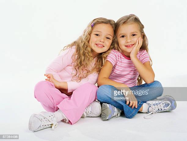 Two young girls sitting on the floor and smiling
