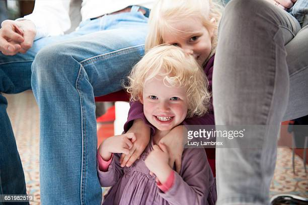 Two young girls sitting under the table