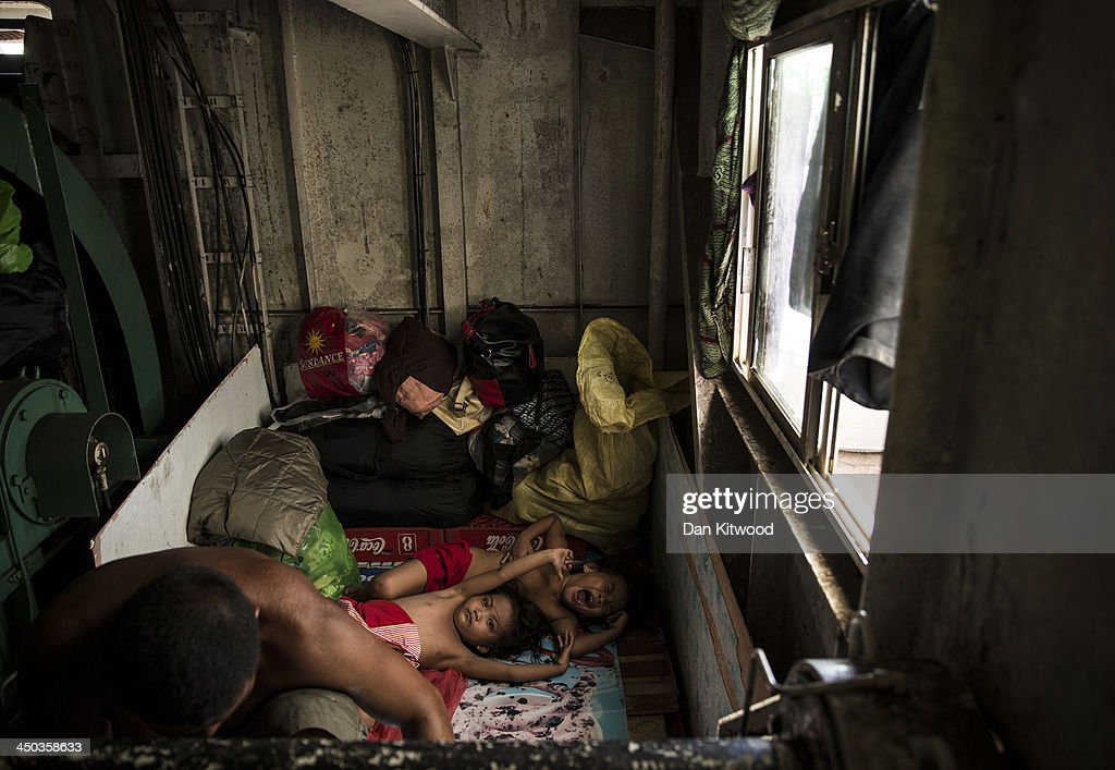 Two young girls sleep in a cabin aboard a tanker in a particularly badly damaged part of Tacloban on November 18 2013 in Leyte Philippines Several...