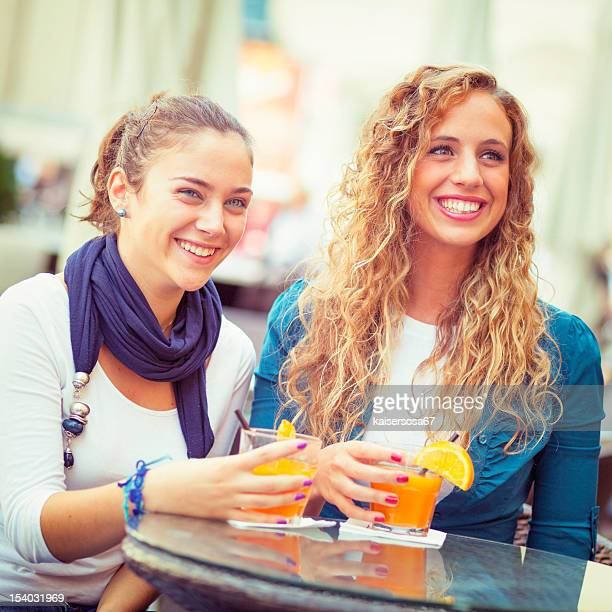 Two young girls smiling and drinking orange juice at bar