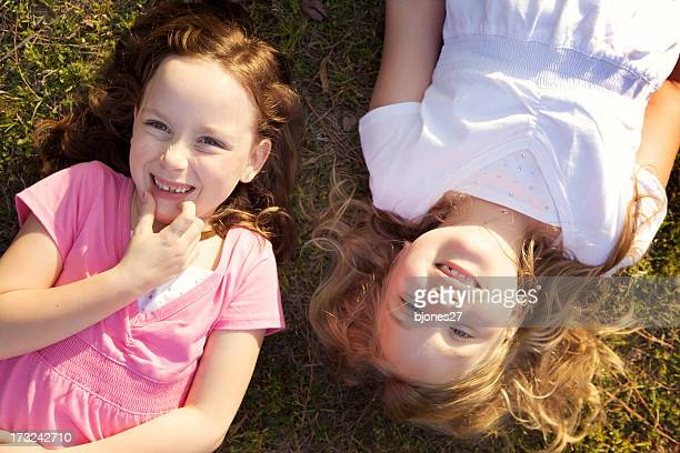 Two young girls smiling and laying in the grass