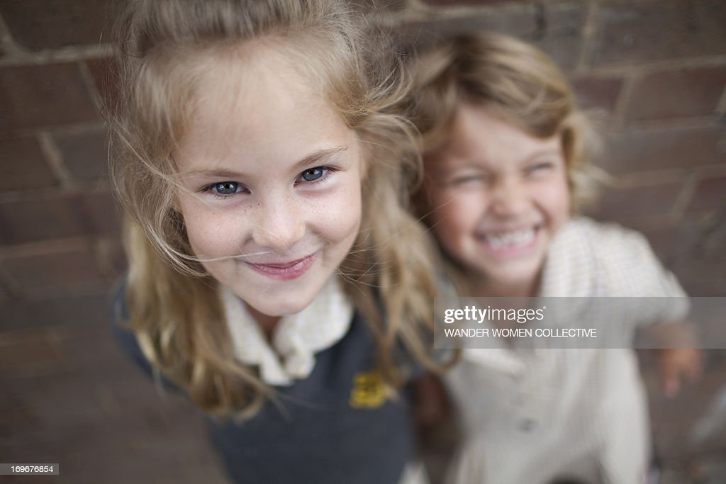 Two young girls smiling at camera school uniform