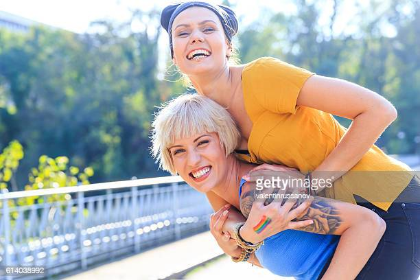 Two young girls standing in piggyback ride on bridge