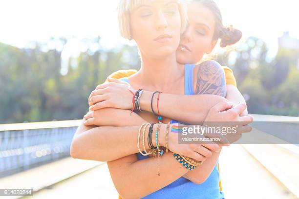 Two young girls standing on bridge and embracing