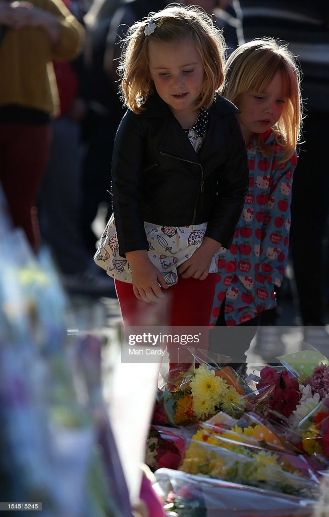 Two young girls stop to look at flowers as they attend a local community memorial vigil outside Ely Fire Station for 32-year-old, Karina Menzies, who was killed in a hit-and-run collision on October 21, 2012 in Cardiff, Wales. Detectives are questioning a 31-year-old man arrested on suspicion of murder after a series of hit-and-runs in Cardiff that left a woman dead and 13 people injured. Nine casualties, five of them children, are still in hospital. Two adults are in critical but stable conditions.